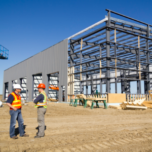 Two construciton workers speaking in front of unfinished steel frame building
